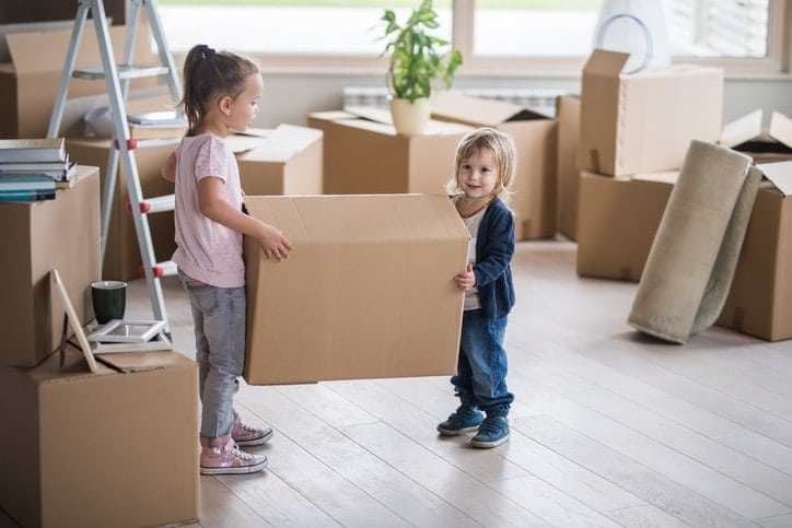 Children helping carring boxes during a house removal